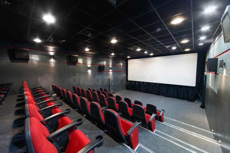 Interior of a small theater with red chairs and screen.  stock photography