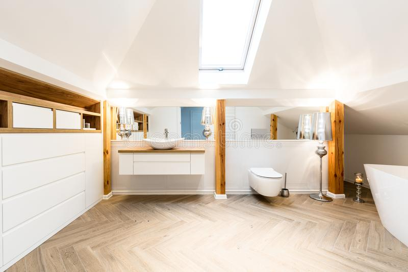 Interior of spacious bathroom. Interior of a spacious bathroom with washbasin, mirror, toilet and wooden beams royalty free stock images
