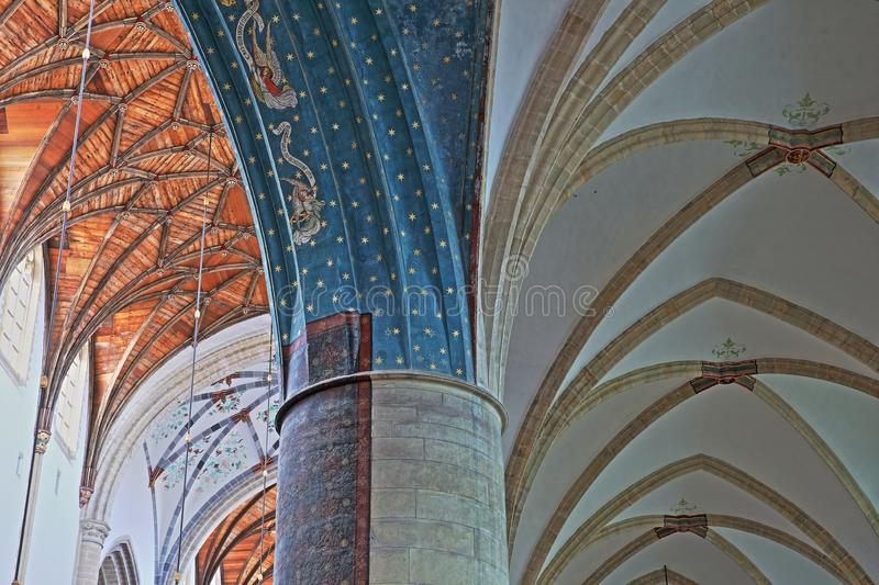 The interior of St Bavokerk Church, with close-up on the vaulted ceiling and a decorated column in the foreground stock photo