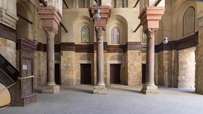 Interior of Sultan Qalawun Mosque with stone columns, colored stained glass windows and wooden doors, Cairo, Egypt royalty free stock photography
