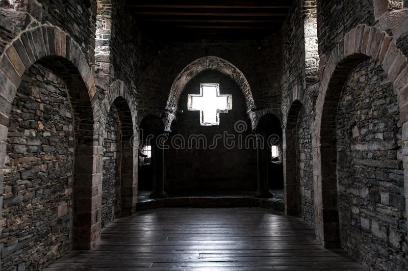 Interior of castle walls with arc. Interior of thick stone made castle walls with arc and window as a cross symbol stock photos