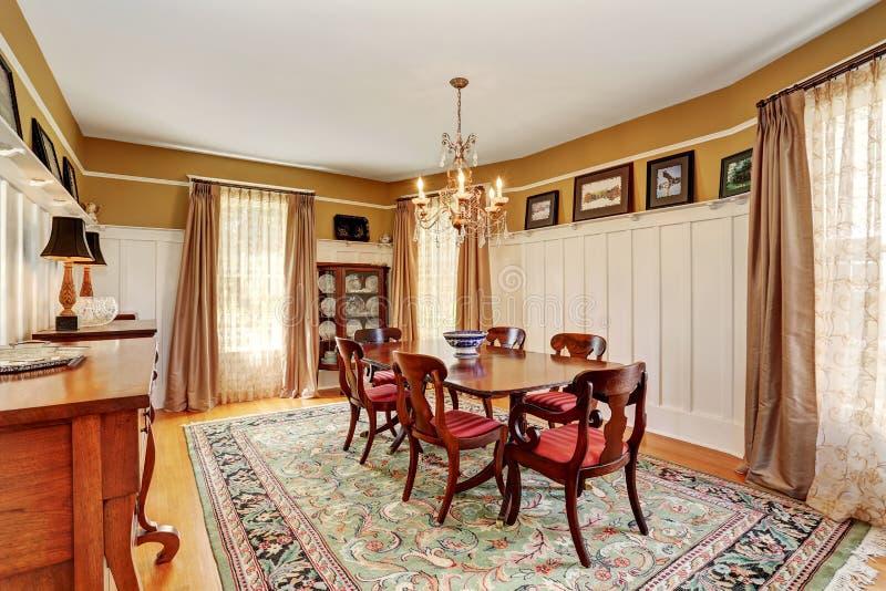 Interior tradicional da sala de jantar com mobília antiga e tapete fotografia de stock royalty free