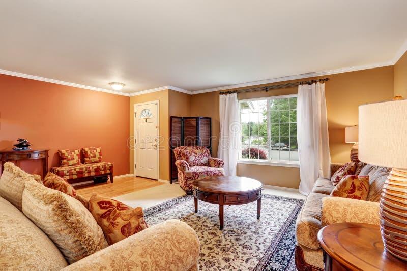 Interior tradicional da sala de visitas com paredes bege, tapete e as cortinas brancas fotos de stock royalty free
