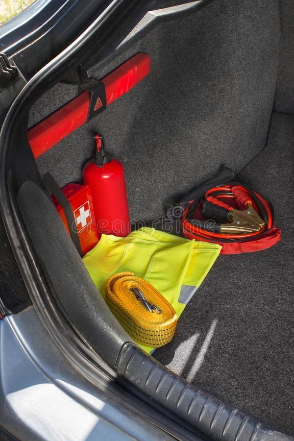 Interior of the trunk of the car in which there is a first aid kit, fire extinguisher, warning triangle, reflective vest, star. The interior of the trunk of the royalty free stock images