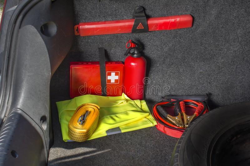 Interior of the trunk of the car in which there is a first aid kit, fire extinguisher, warning triangle, reflective vest, star. The interior of the trunk of the royalty free stock photo