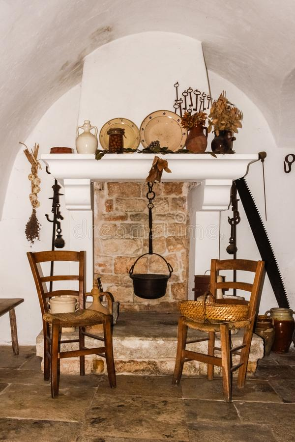 Traditional Trulli. Interior. Alberobello. Apulia. Italy. Interior. Typical trulli. fireplace with chairs and decorated plates. Alberobello. Apulia. Italy royalty free stock images