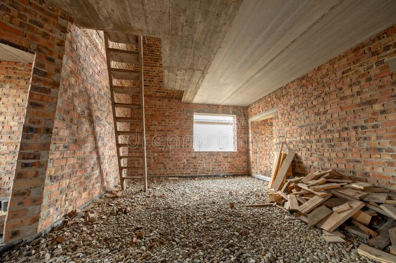 Interior of unfinished brick house with concrete floor and bare walls ready for plastering under construction. Real estate royalty free stock photography