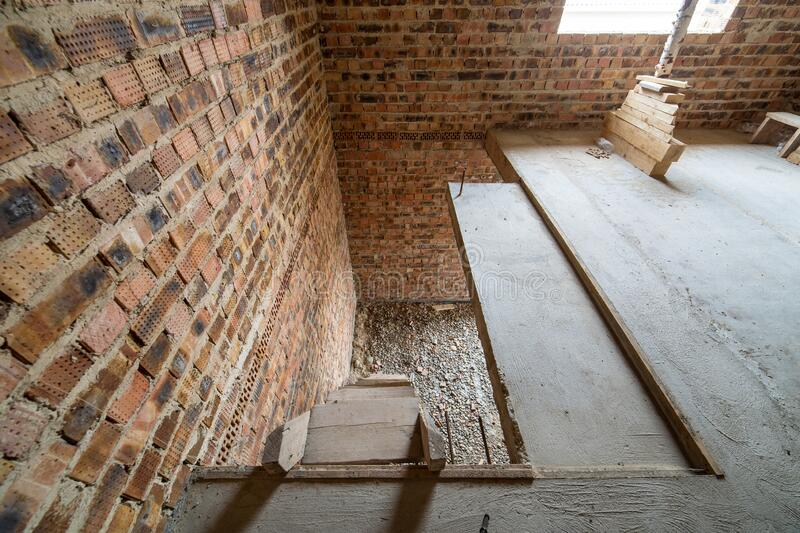 Interior of unfinished brick house with concrete floor and bare walls ready for plastering under construction. Real estate royalty free stock photos
