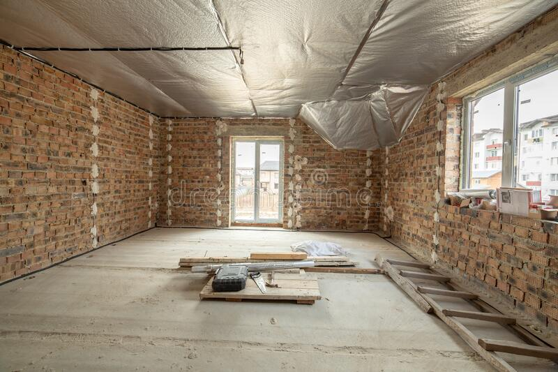 Interior of unfinished brick house with concrete floor and bare walls ready for plastering under construction. Real estate stock image