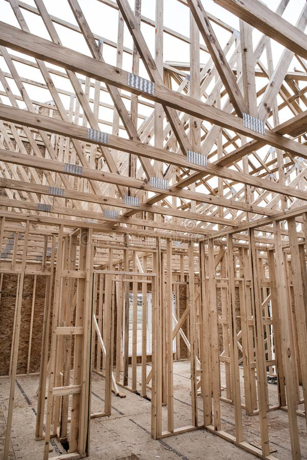 Interior of unfinished new home construction work site walls and roof trusses built from 2x4`s. Interior of new home construction work site walls and roof stock photo