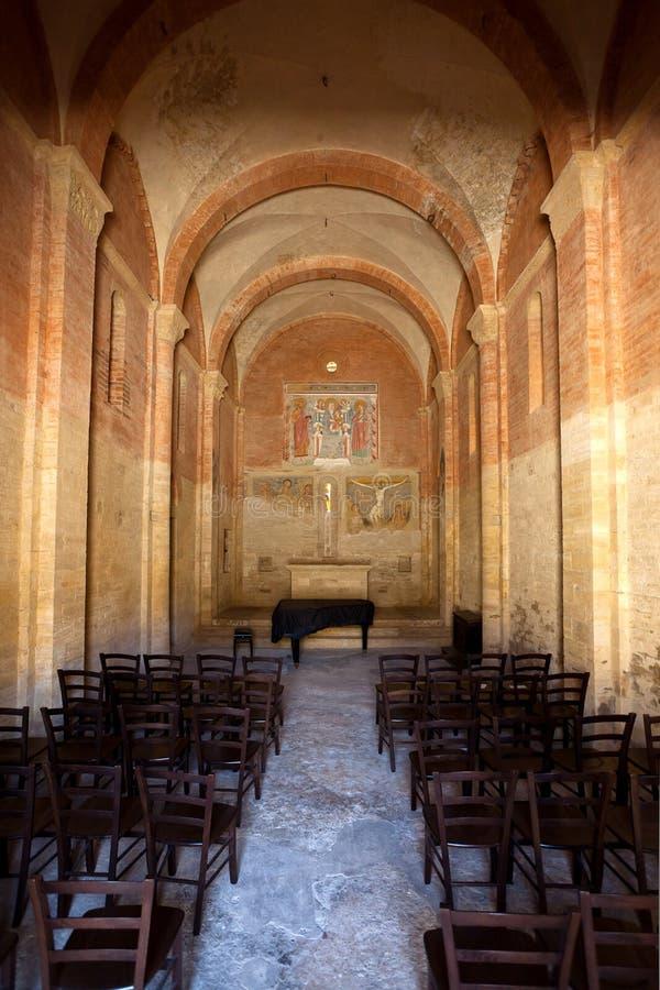 Interior chiesa di San Jacopo al Tempio Templar church Saint James, San Gimignano, Siena, Italy. The interior with vaults, pillars, fresco and chairs of the royalty free stock image