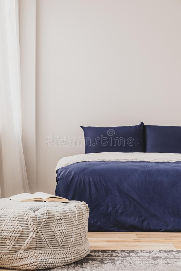 Interior vazio do quarto com simples cama azul e livro na bolsa, espaço de cópia na parede imagem de stock royalty free