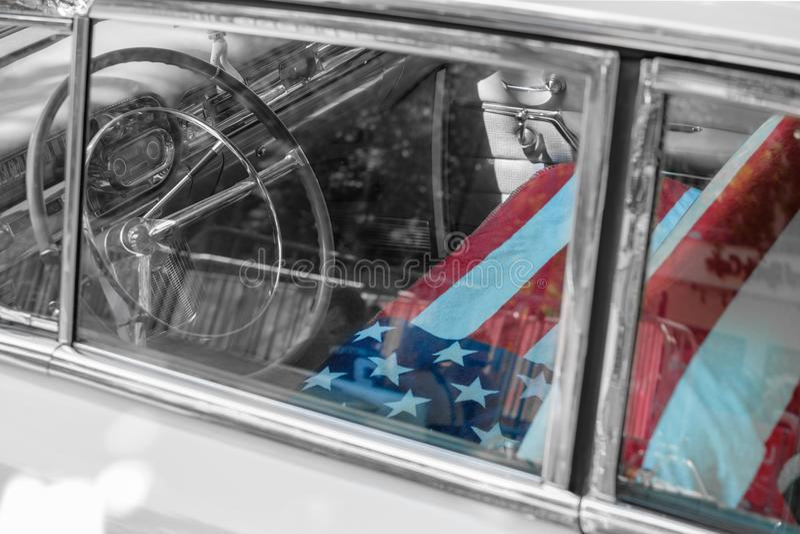 Interior velho do carro do oldtimer de Cadillac com a bandeira americana em s dianteiro foto de stock royalty free