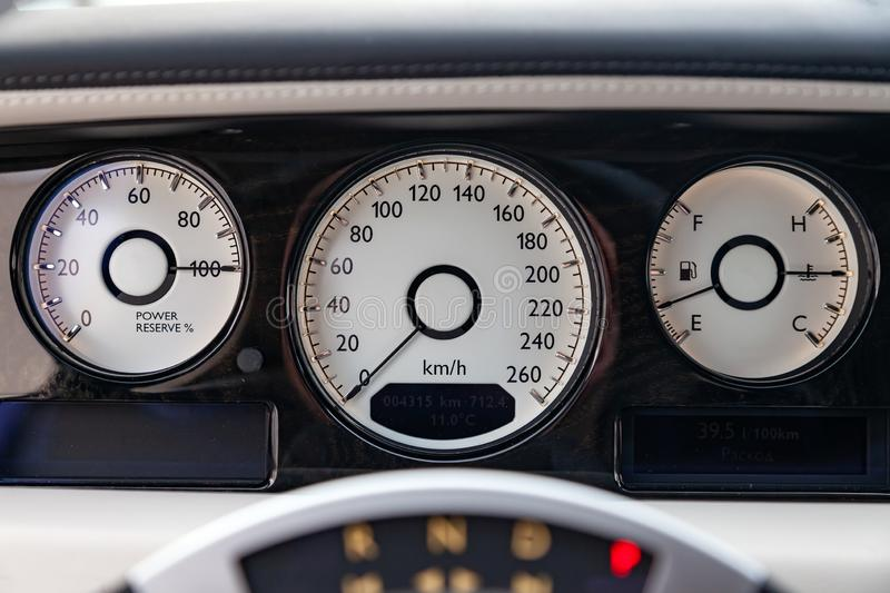 Interior view of new a very expensive car, a long black limousine with dashboard, speedometer and tachometer. On parking stock image