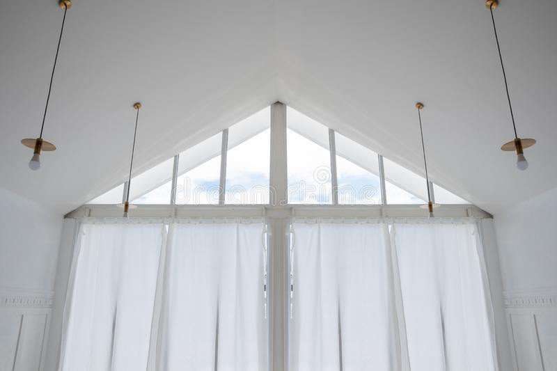 Interior view of triangle shape window with white curtain and cloud sky. Interior view of triangle shape glass window with white curtain and cloud sky royalty free stock images