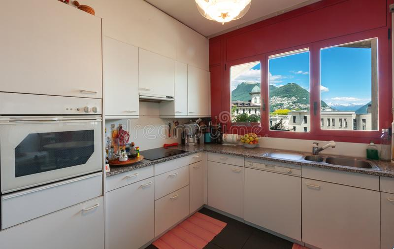 Interior of vintage apartment, nobody inside. kitchen. Interior of vintage apartment. White kitchen with red windows and view on city royalty free stock images