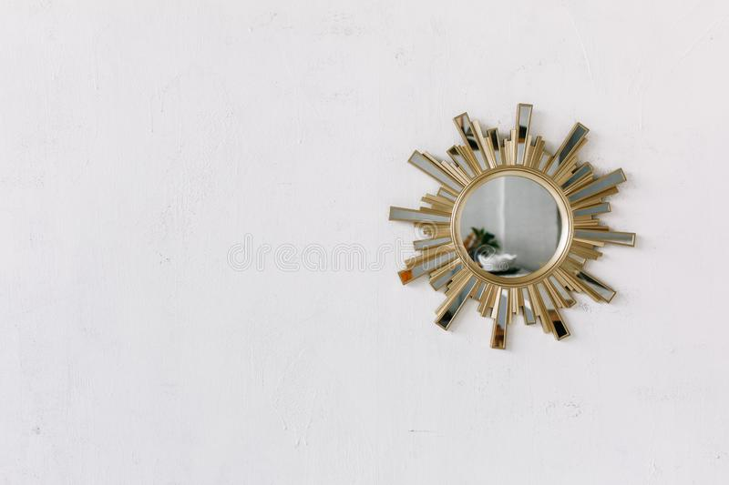 Interior wall mirror in the shape of a sun with metal brass sun rays as the frame isolated on white rustic wall. Background royalty free stock photography