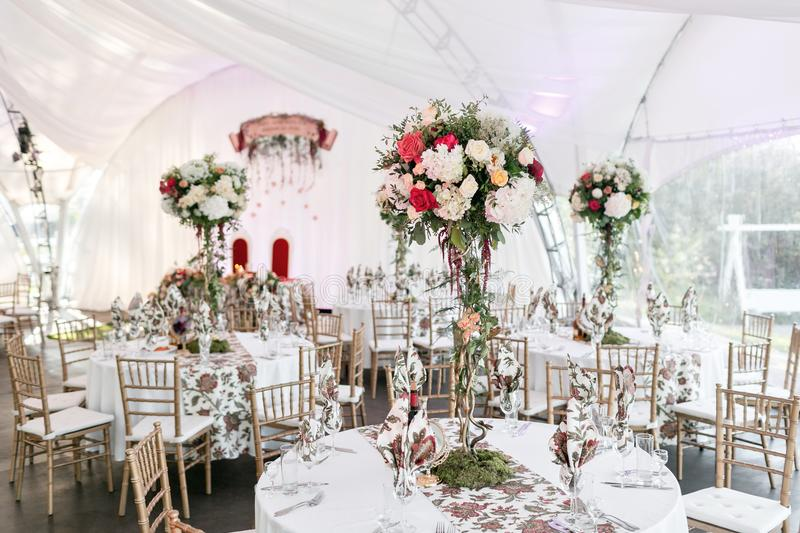Interior of a wedding tent decoration ready for guests. Served round banquet table outdoor in marquee decorated flowers stock photo
