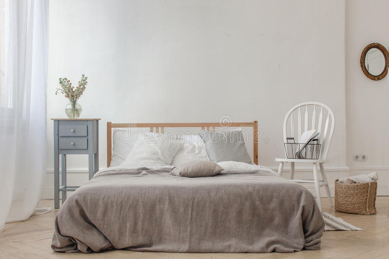 Interior of white and gray cozy bedroom. With chair, basket, flowers, bedside table and mirror royalty free stock photography