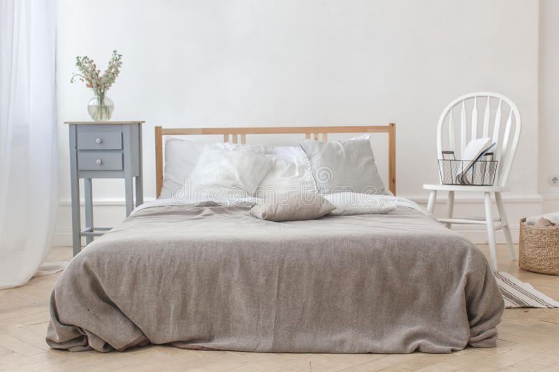 Interior of white and gray cozy bedroom. With chair, basket, flowers, bedside table and mirror royalty free stock photo