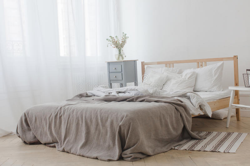 Interior of white and gray cozy bedroom. With chair, basket, flowers, bedside table and mirror stock image