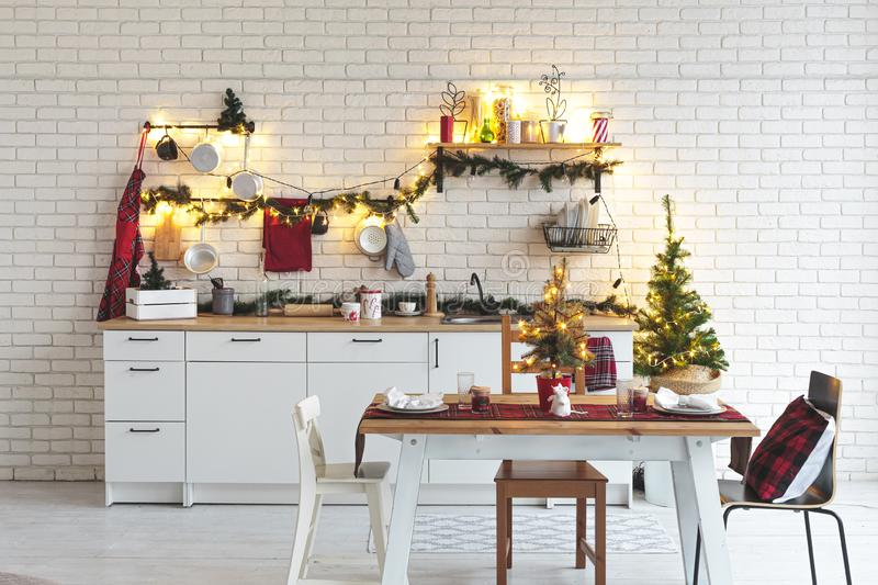 Interior white kitchen with lights and red christmas decorations royalty free stock photo