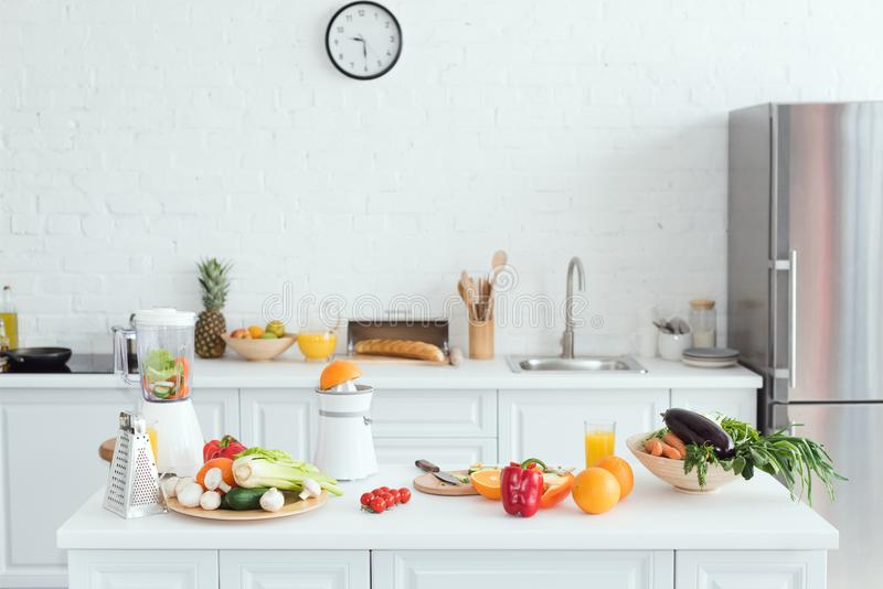 interior of white light kitchen with delicious fruits and vegetables royalty free stock images