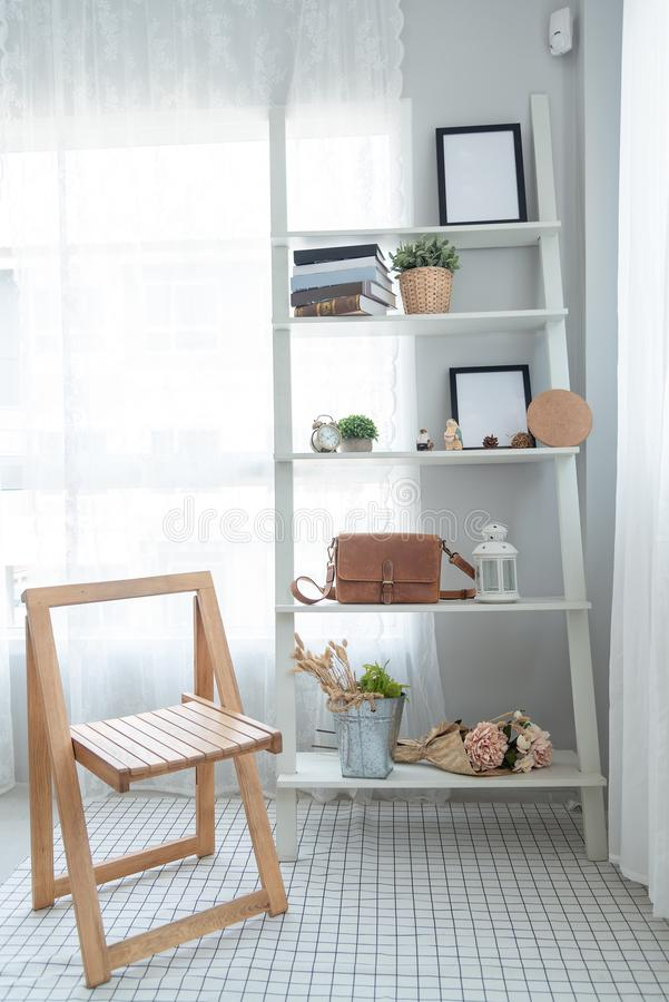 Interior white minimalist style with a wooden chair and a wooden shelf in living room .Decoration modern lifestyle concept royalty free stock photos