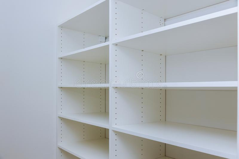 Interior of white plastic cabinet or clothing with many empty shelves with installation stock images