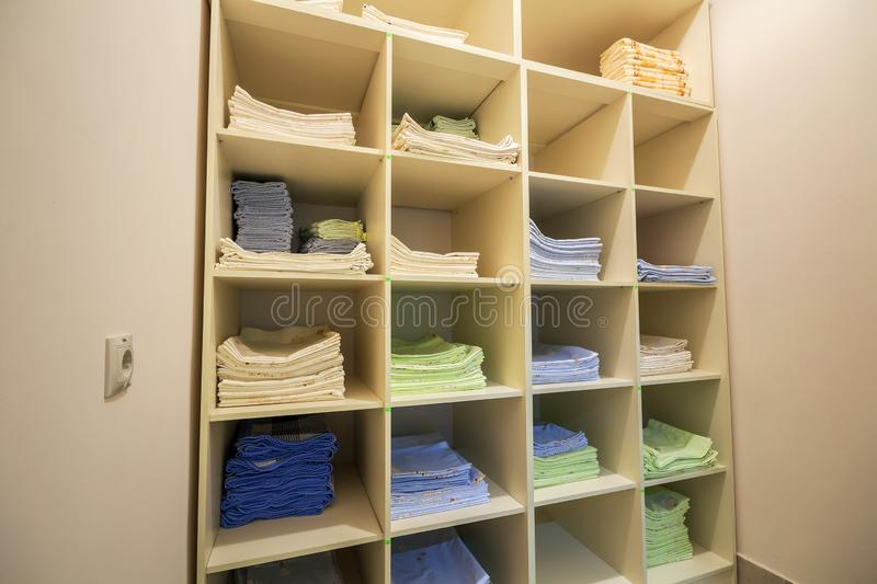 Interior of white plastic cabinet or clothing open wardrobe with stacked piles of clean colorful linen on shelves. Furniture stock photos