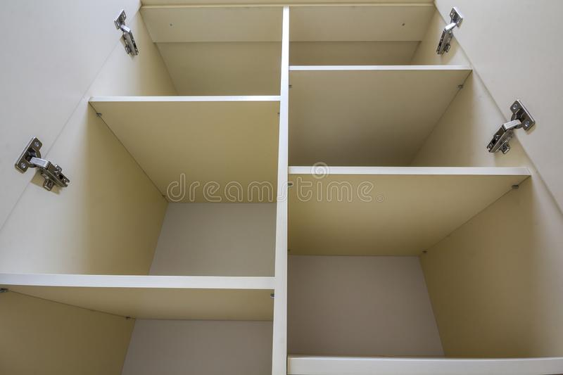 Interior of white plastic cabinet or clothing wardrobe with many empty shelves with open doors. Furniture design and installation.  royalty free stock photo