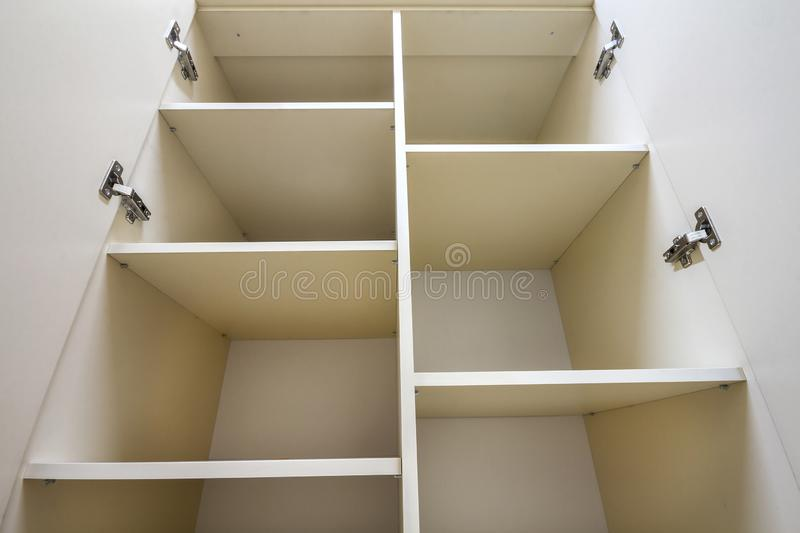 Interior of white plastic cabinet or clothing wardrobe with many empty shelves with open doors. Furniture design and installation.  royalty free stock images