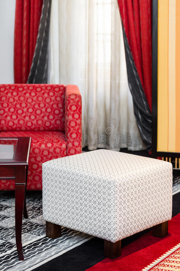 Interior with white pouffe and red sofa. Interior with white vintage pouffe and red sofa stock photos