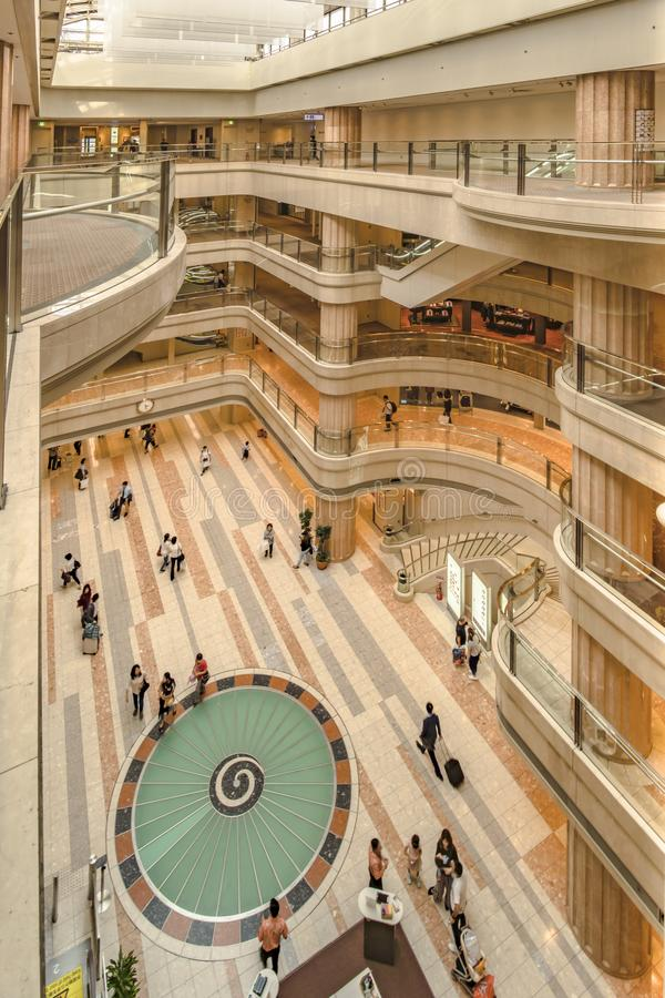 Interior wide view of the Haneda Airport Market Place with a turbine design decoration on floor and atirum on top.  stock photography
