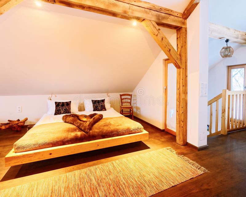 Interior of wood bedroom Modern design of bed. Interior of wood bedroom. Modern design of bed. Wooden furniture of room. Home decor. House apartment. Cozy style stock image