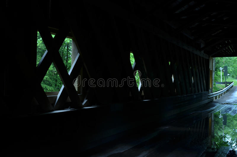 Interior Wooden covered bridge on rural road in Ohio, USA. Interior Wooden covered bridge built in 1867 in the Town Lattice style sits atop cut stone abutments stock images