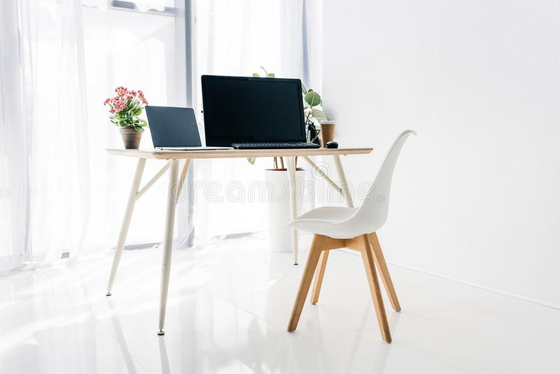 Interior of workplace with chair, potted plants, laptop and computer. On table stock photos