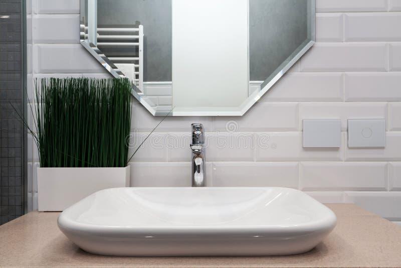 Interiore della stanza da bagno Bagno luminoso con le nuove mattonelle Nuovo lavandino, lavandino bianco e grande specchio fotografia stock libera da diritti