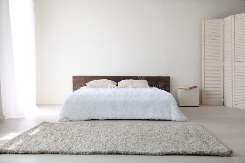 Interiores brillantes del dormitorio blanco con la cama fotos de archivo