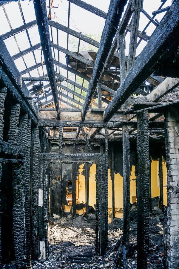Interiores queimados da casa após o fogo Tetos e apoios carbonizados Paredes de madeira queimadas fotografia de stock royalty free