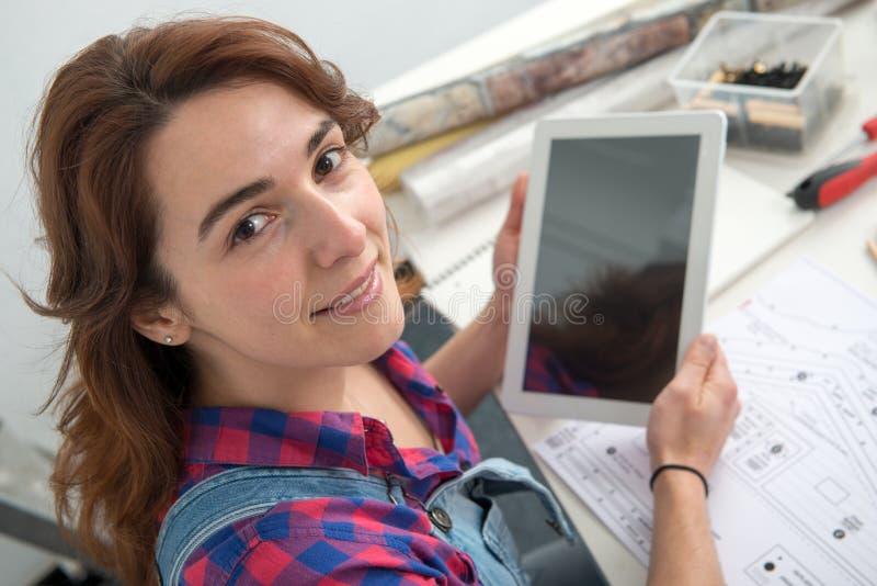 Interiorista de la mujer joven que se sienta en el escritorio usando tabl digital imagen de archivo