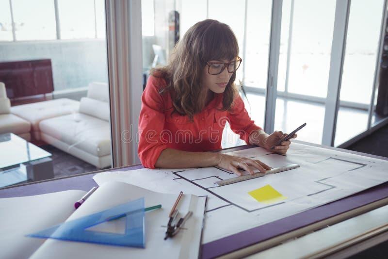 Interiorista de sexo femenino que hace planes en los papeles imagen de archivo