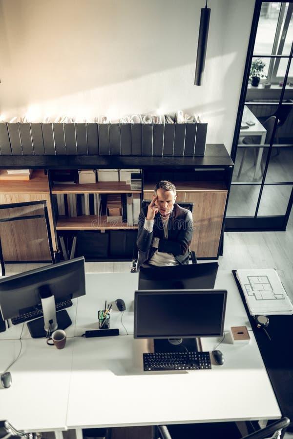 Interiorista ocupado que se sienta delante de la sensaci?n del ordenador pensativa fotografía de archivo