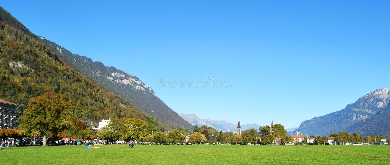 Interlaken, Suíça, montanhas, casas e campo enorme da jarda do gramado fotos de stock royalty free