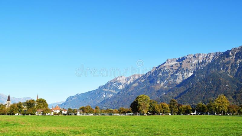 Interlaken, Zwitserland, Bergen, huizen en het reusachtige gebied van de gazonyard royalty-vrije stock fotografie