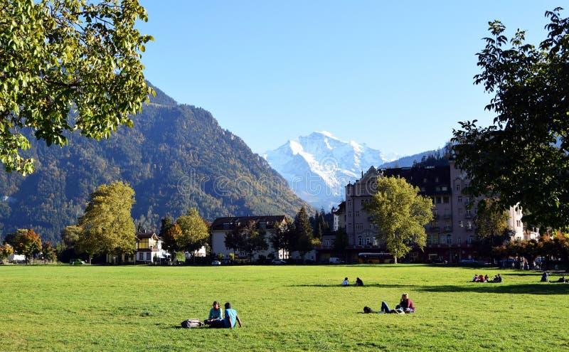 Interlaken, Zwitserland, Families en vrienden die pret hebben bij de tuin van het theegazon stock afbeelding