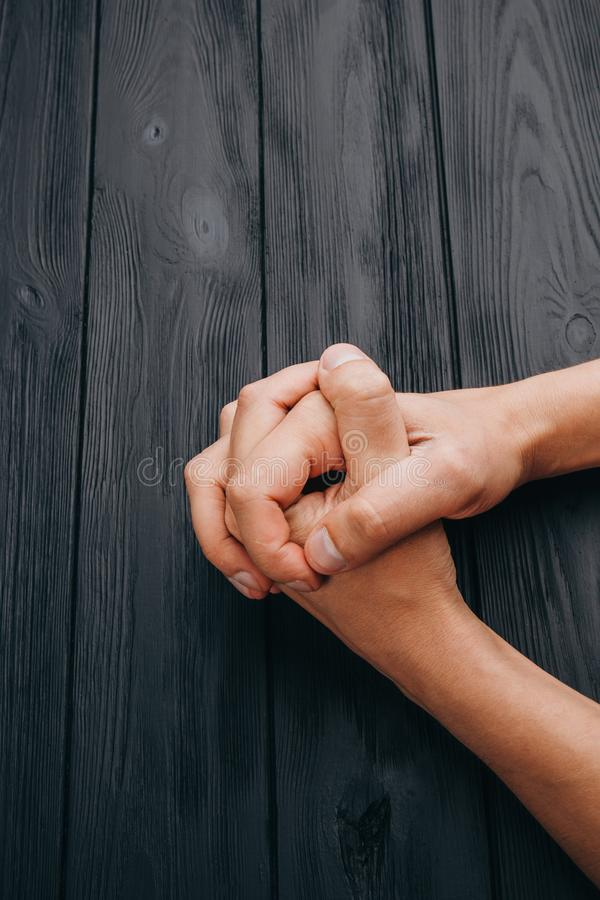 Interlocked fingers, white male hands interlocked on black rustic wood table close up. top view. a man is waiting for negotiations royalty free stock photos