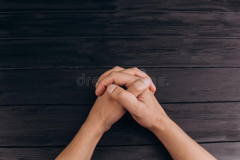 Interlocked fingers, white male hands interlocked on black rustic wood table close up. top view. a man is waiting for negotiations royalty free stock images