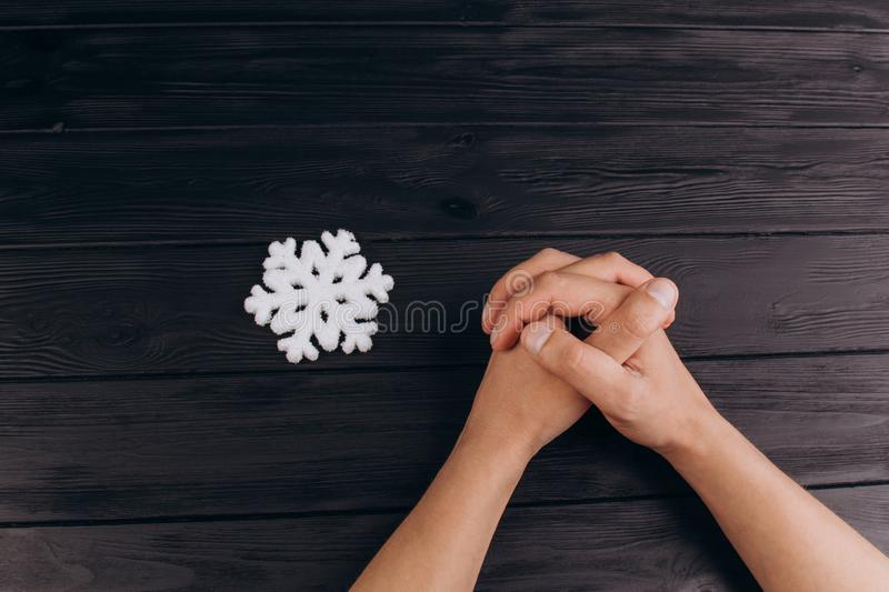 Interlocked fingers, white male hands interlocked on black rustic wood table close up. top view. a man is waiting for negotiations royalty free stock photography