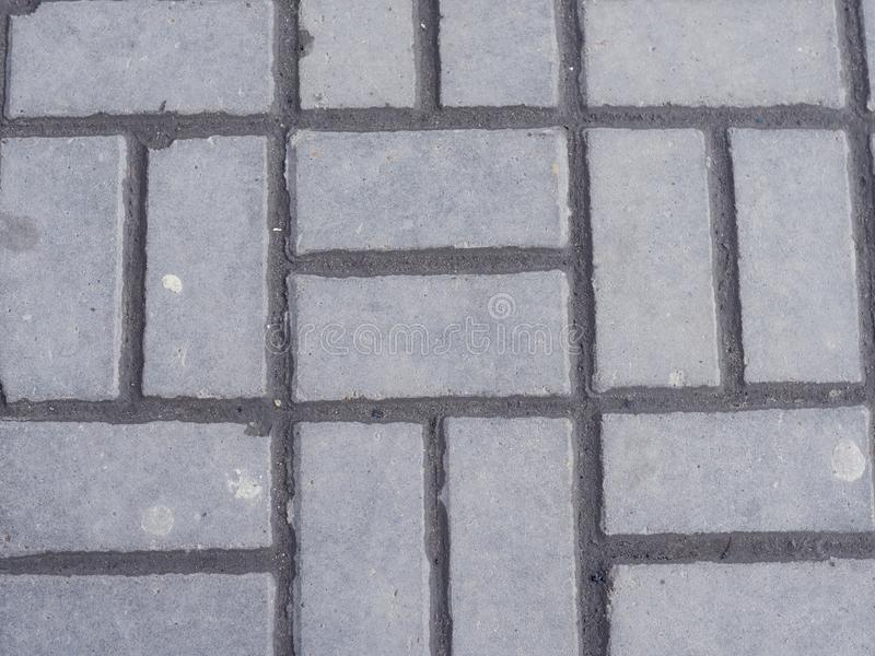 Interlocking paving with gray and white concrete blocks Concrete products Construction industry Paved ground royalty free stock photos
